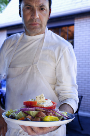 Portrait of a chef serving me a Greek salad
